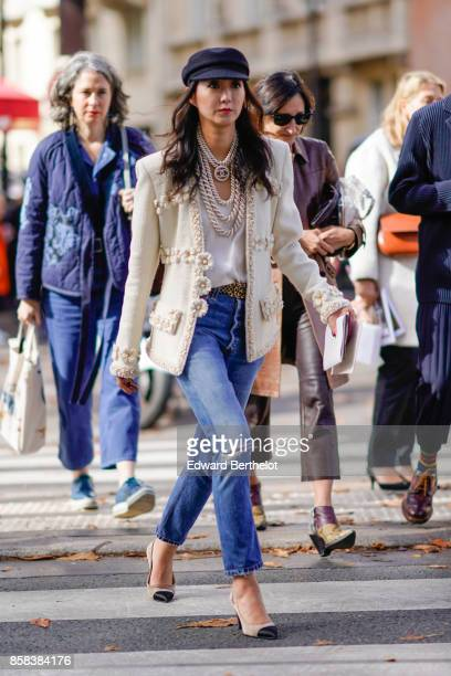 A guest wears a beret hat a Chanel white jacket Chanel necklace a white top blue ripped jeans Chanel slingback shoes outside Moncler during Paris...