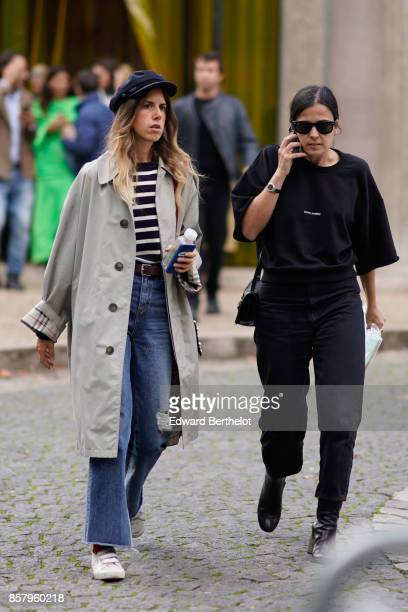 A guest wears a beret hat a gray jacket a striped top blue flare jeans white sneakers a guest wears sunglasses a black oversize tshirt black pants...