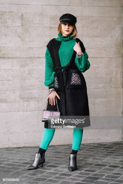 Guest wears a beret hat, a green pull over, a black dress, green pants, a glitter bag, glitter shoes, during London Fashion Week February 2018 on...