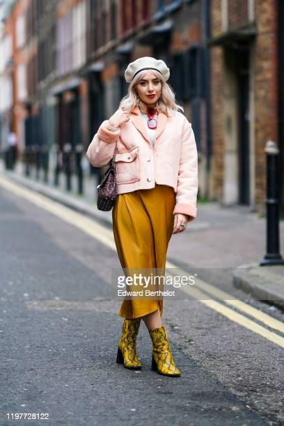 A guest wears a beret hat a pink aviator jacket with sheep wool inner lining red sunglasses a burgundy studded bag an orange lustrous skirt yellow...