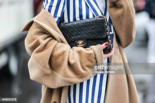 A guest wears a beret hat a striped jacket striped skirt a white turtleneck top a beige coat a Chanel bag and yellow heels outside the Valentino show...