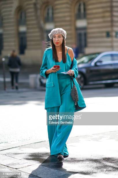A guest wears a beret hat a turquoise tank top a blue blazer jacket oversized flare pants a bag outside Redemption during Paris Fashion Week...