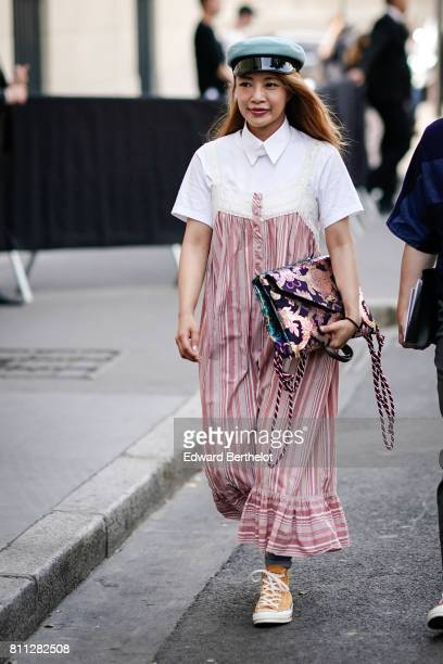 A guest wears a beret hat a white tshirt a flare ruffle striped jumpsuit orange sneakers with white shoelace outside the Valentino show during Paris...