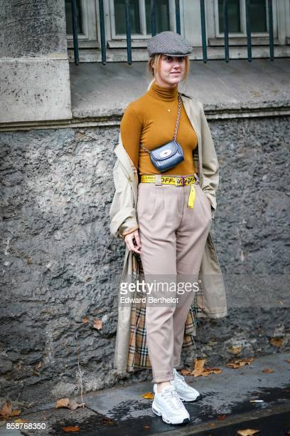 A guest wears a beret hat an orange turtleneck top gray pants sneakers a gray coat with inner tartan outside Valentino during Paris Fashion Week...
