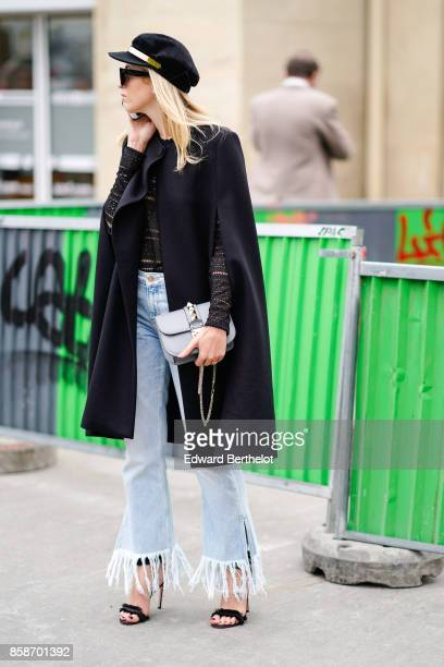 A guest wears a beret hat sunglasses a black coat ripped jeans with fringes black shoes outside Giambattista Valli during Paris Fashion Week...