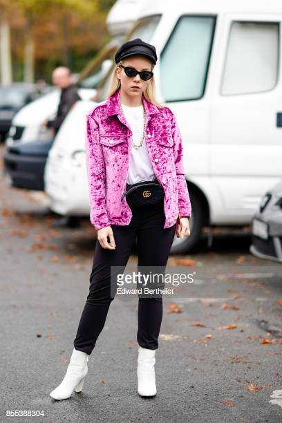 A guest wears a beret hat sunglasses a pink jacket white top black pants white boots outside Manish Arora during Paris Fashion Week Womenswear...