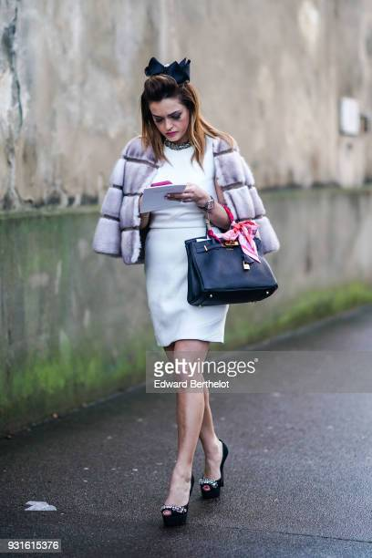 A guest wears a big black bow in her hair a light grey fur coat a rhinestone embroidered collar white dress a black Hermes handbag a red scarf...