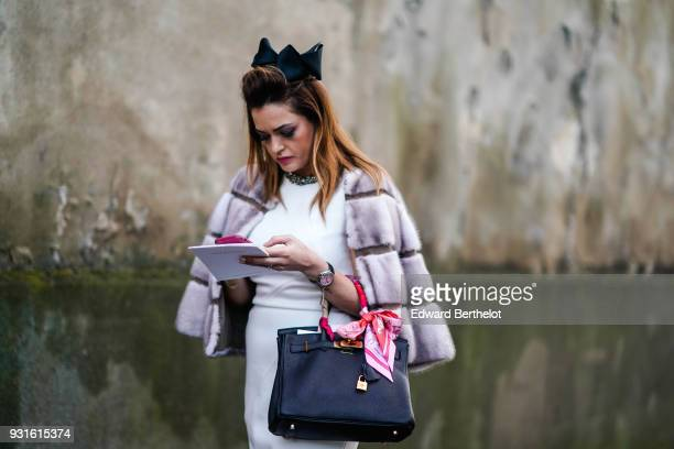 A guest wears a big black bow in her hair a light grey fur jacket a red scarf a white dress with a rhinestone embroidered collar and a black Hermes...