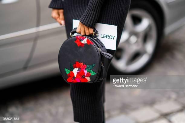 A guest wears a blac bag with red flower print during Paris Fashion Week Womenswear Fall/Winter 2018/2019 on March 3 2018 in Paris France
