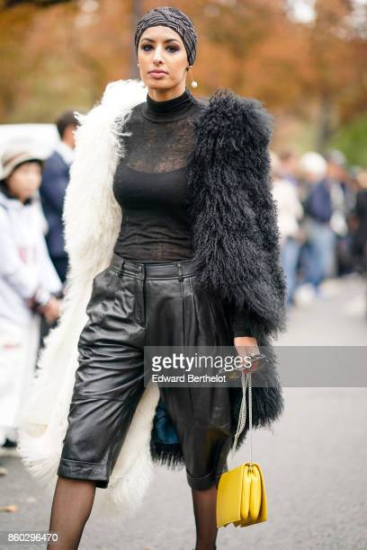 A guest wears a black and beige turban a black and white fur coat a black turtleneck top black leather bermuda shorts a yellow bag outside Lanvin...