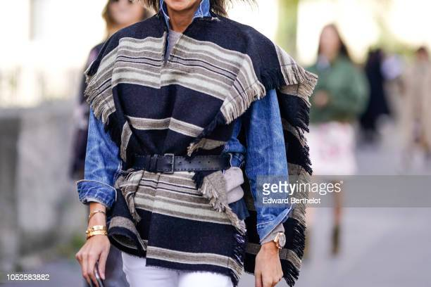 Guest wears a black and brown fringed poncho jacket, a black leather belt, a blue denim top, white pants, outside Haider Ackermann, during Paris...