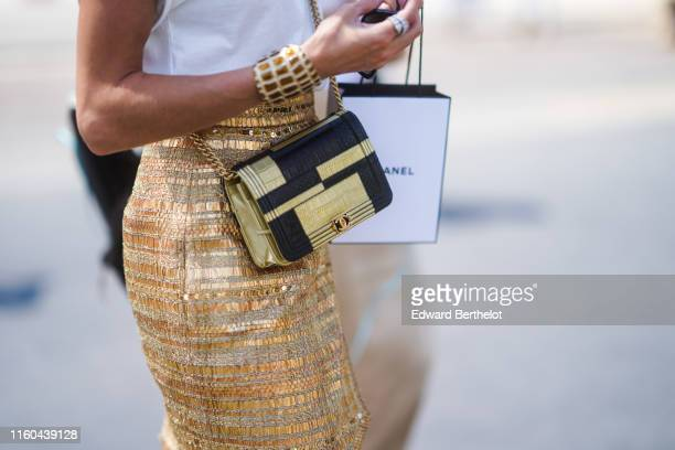 A guest wears a black and golden Chanel bag outside Chanel during Paris Fashion Week Haute Couture Fall/Winter 2019/2020 on July 02 2019 in Paris...