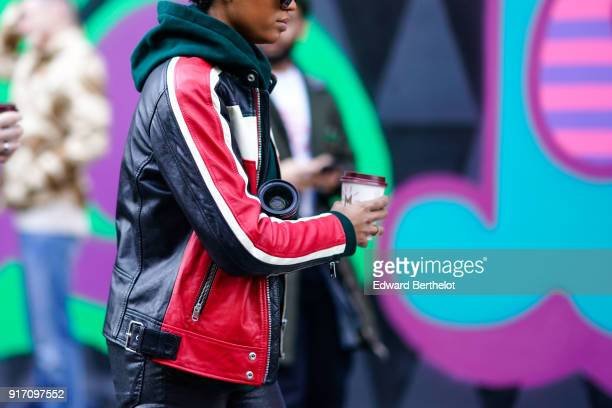 A guest wears a black and red leather jacket during London Fashion Week Men's January 2018 at on January 6 2018 in London England