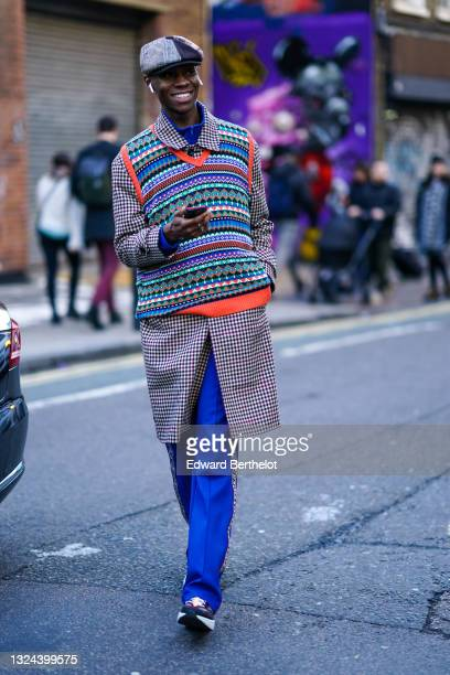 Guest wears a black and white and red checkered side and an houndstooth fabric side beret hat, a pearl earring, a bold blue zipper turtleneck...