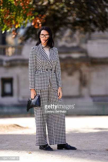 A guest wears a black and white checked blazer jacket flare suit pants black shoes glasses a black crocodile bag with fringes outside Elie Saab...
