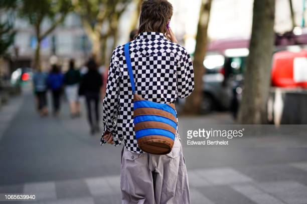 A guest wears a black and white checked jacket a blue and brown striped bag outside Issey Miyake during Paris Fashion Week Menswear SpringSummer 2019...