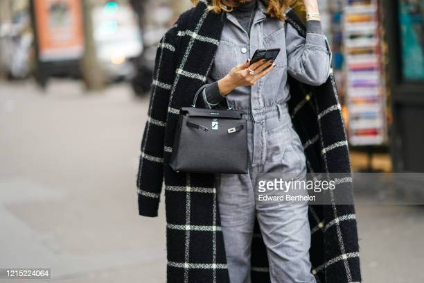 Guest wears a black and white checked pattern plaid long coat, a Hermes bag, a denim jumpsuit, a turtleneck top, outside Ralph & Russo, during Paris...
