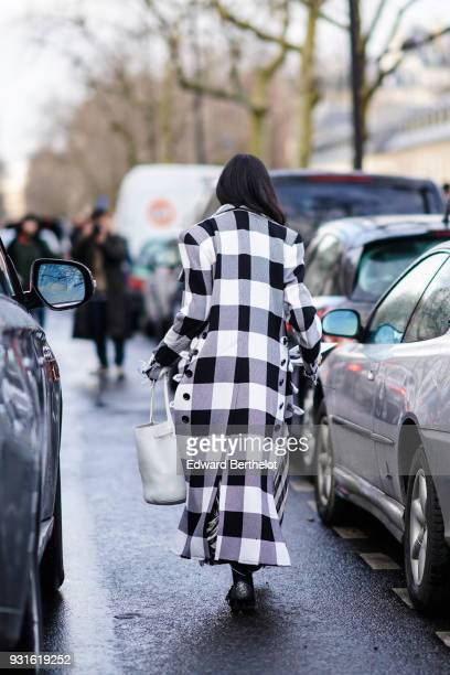 A guest wears a black and white checked plaid coat with eyelets on the sides a large white tote bag outside Valentino during Paris Fashion Week...