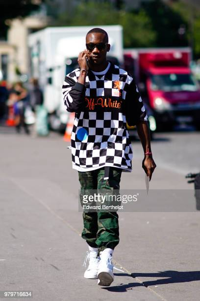 A guest wears a black and white checked tshirt from OffWhite military camouflage print pants sunglasses outside OffWhite during Paris Fashion Week...