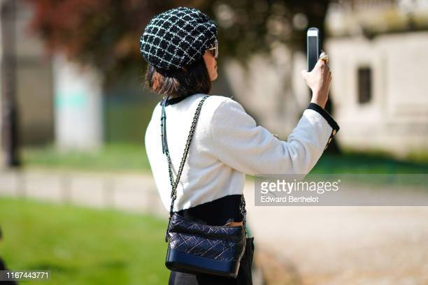 A guest wears a black and white checked tweed beret hat sunglasses a Chanel rhinestone necklace a black trimmed white Chanel jacket a black Chanel...