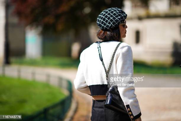 A guest wears a black and white checked tweed beret hat sunglasses a black trimmed white Chanel jacket a black Chanel bag outside the Chanel Cruise...