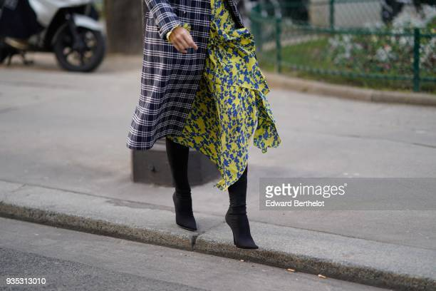A guest wears a black and white checkered coat a flowy blueprint yellow pleated layerdress black highheeled pointy toe boots during Paris Fashion...