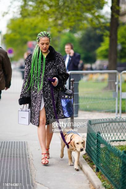 A guest wears a black and white coat with fur collar and cuffs a shiny blue sequined studded bag red strappy sandals outside the Chanel Cruise...