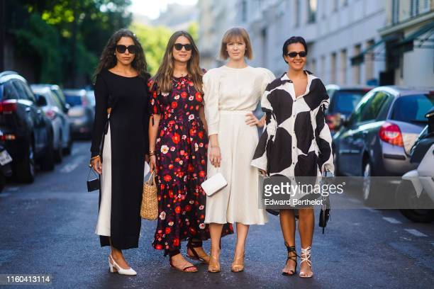 A guest wears a black and white dress a guest wears a purple and red floral print dress a basket bag Vika Gazinskaya wears a white dress and a bag a...