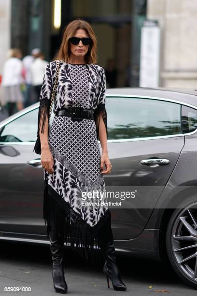 A guest wears a black and white dress with printed features outside Andrew GN during Paris Fashion Week Womenswear Spring/Summer 2018 on September 29...