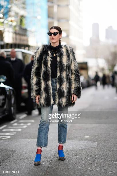 A guest wears a black and white faux fur coat cropped jeans sunglasses shoes blue socks a black turtleneck top a necklace during London Fashion Week...