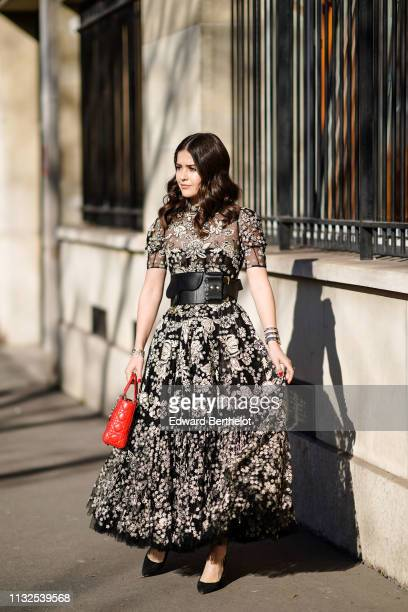 A guest wears a black and white floral print ruffled and gathered dress with a black and white floral lace top a black Dior belt wristlets a red Lady...