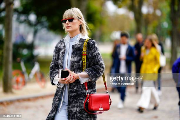 A guest wears a black and white fluffy coat a red bag a yellow shoulder strap red shoes sunglasses outside Beautiful People during Paris Fashion Week...