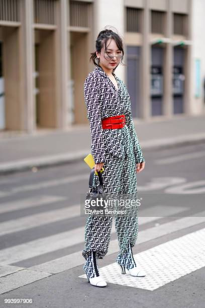 Guest wears a black and white full Fendi outfit, made of a blazer jacket with Fendi printed logos, pants, boots, a black mini bag, sunglasses , a red...