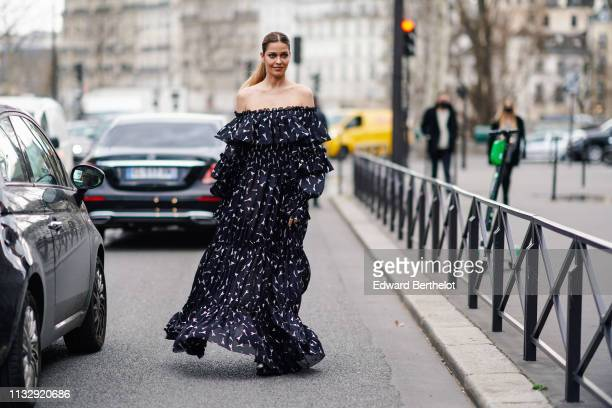 A guest wears a black and white gathered and ruffled offtheshoulder gown outside Redemption during Paris Fashion Week Womenswear Fall/Winter...