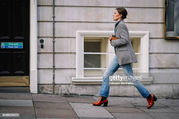 A guest wears a black and white gingham blazer jacket blue jeans red boots outside Peter Pilotto during London Fashion Week September 2017 on...