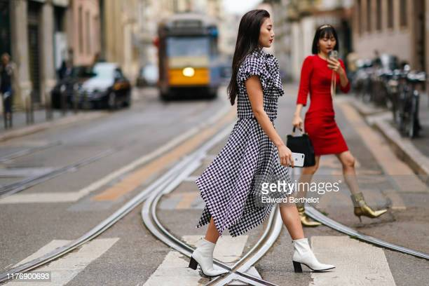 Guest wears a black and white houndstooth top with puff sleeves and a lavaliere, a black and white houndstooth handkerchief skirt, white pointy ankle...