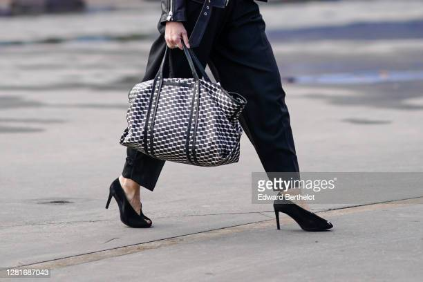 Guest wears a black and white leather bag with printed geometric patterns, black high heeled pointy shoes, pants, outside Chanel, during Paris...