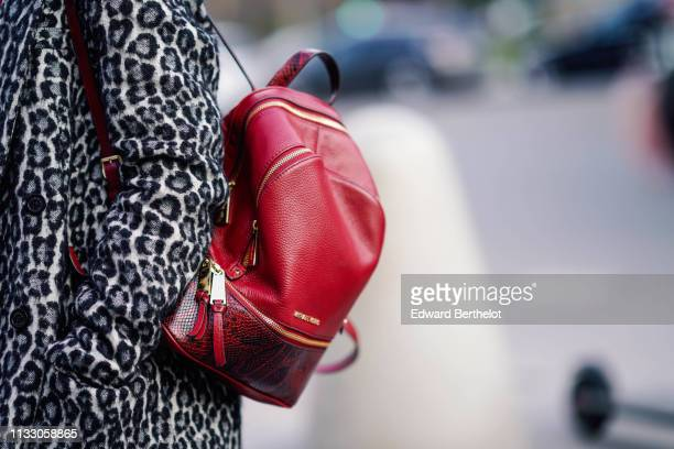 A guest wears a black and white leopard print coat a red Michael Kors backpack outside Paco Rabanne during Paris Fashion Week Womenswear Fall/Winter...
