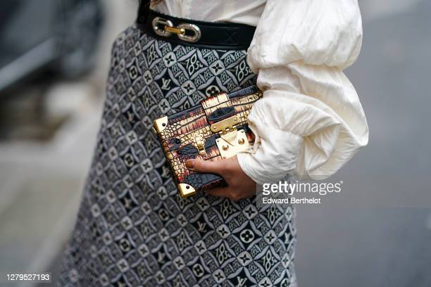 Guest wears, a black and white monogram Vuitton skirt, a Vuitton Petite Malle rigid case bag, a white top with puff sleeves, outside Louis Vuitton,...