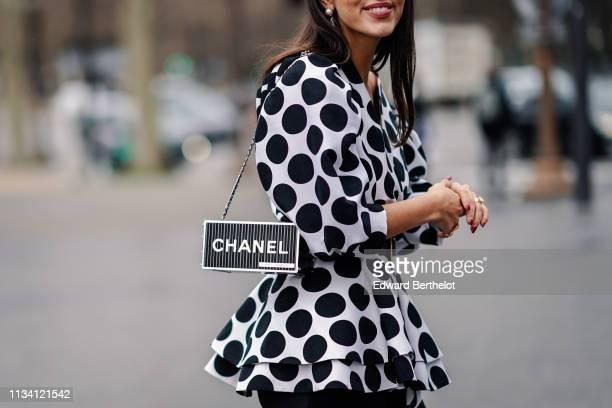 Guest wears a black and white polka dots printed dress, a Chanel rectangular rigid bag, a belt, outside Chanel, during Paris Fashion Week Womenswear...