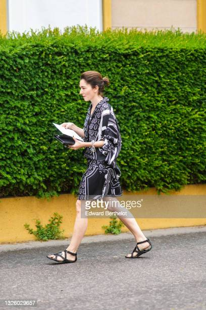 Guest wears a black and white print pattern oversized shirt and shorts jumpsuit, a black shiny leather clutch from Hermes, a silver ring, a large...