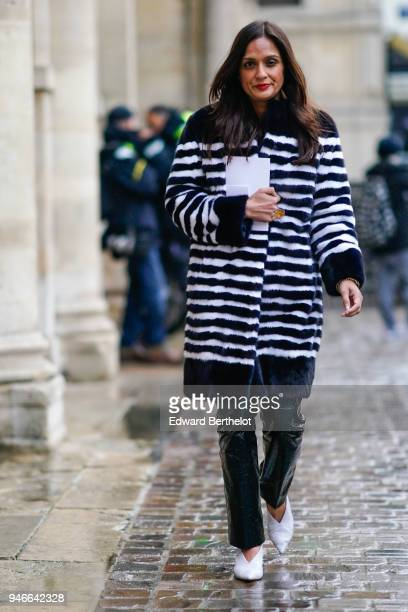 A guest wears a black and white striped coat black pvc pants white shoes outside Thom Browne during Paris Fashion Week Menswear Fall Winter 20182019...