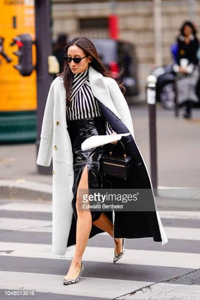 A guest wears a black and white striped shirt a black leather skirt shoes a black bag a gray coat sunglasses outside Miu Miu during Paris Fashion...
