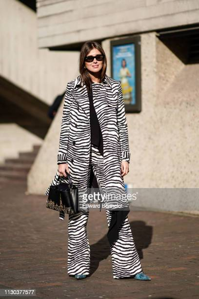 A guest wears a black and white zebra print jacket a bag with embroidered features depicting Paris and the Eiffel tower flare pants sunglasses during...