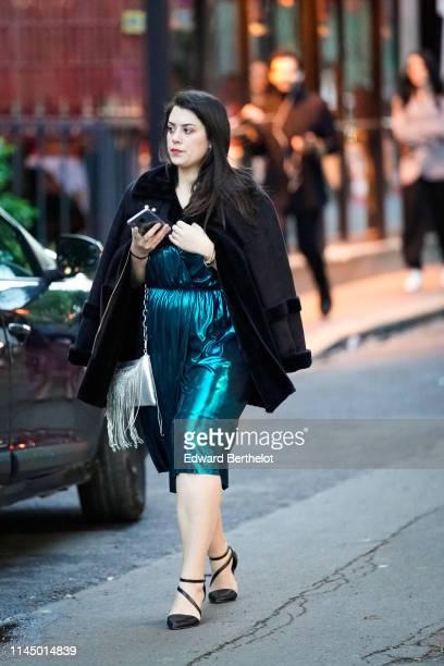 A guest wears a black aviator jacket a blue glitter shiny silky dress black shoes a silver fringed bag outside the Scandal A Paris JeanPaul...
