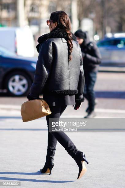 A guest wears a black aviator jacket black pants black shoes during Paris Fashion Week Womenswear Fall/Winter 2018/2019 on February 28 2018 in Paris...