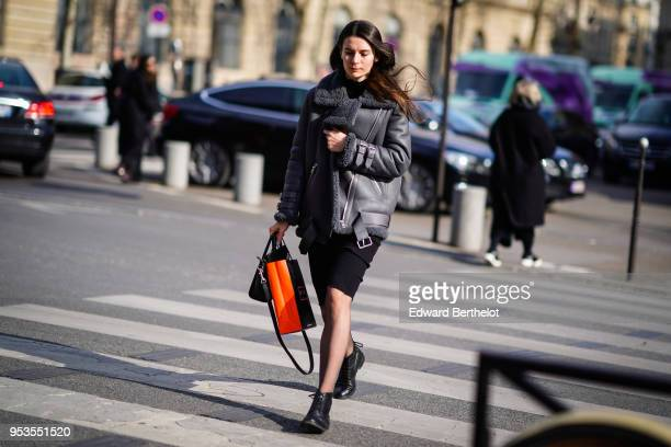 A guest wears a black aviator jacket with sheep wool a black skirt black shoes during Paris Fashion Week Womenswear Fall/Winter 2018/2019 on February...