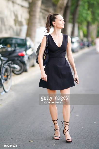 A guest wears a black bag a black minidress with a deep cleavage black gladiator sandals outside the Kerastase Party At Port Debilly on June 26 2019...