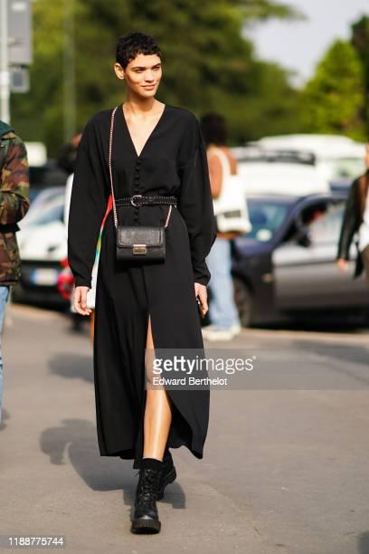 Guest wears a black bag, a black studded belt, a black v-neck drop-shoulder front-split long coat, black army-style boots, outside the Tod's show...