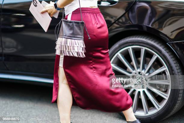 A guest wears a black bag with fringes outside Acne Studios during Paris Fashion Week Womenswear Fall Winter 2019 on July 1 2018 in Paris France